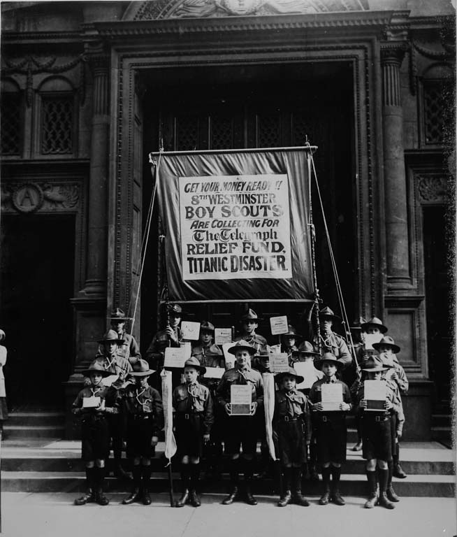 "A group of scouts pictured together in London holding a large banner which reads""Get your money ready! 8th Westminster Boy Scouts are collecting for the Telegraph Relief Fund, Titanic disaster""."