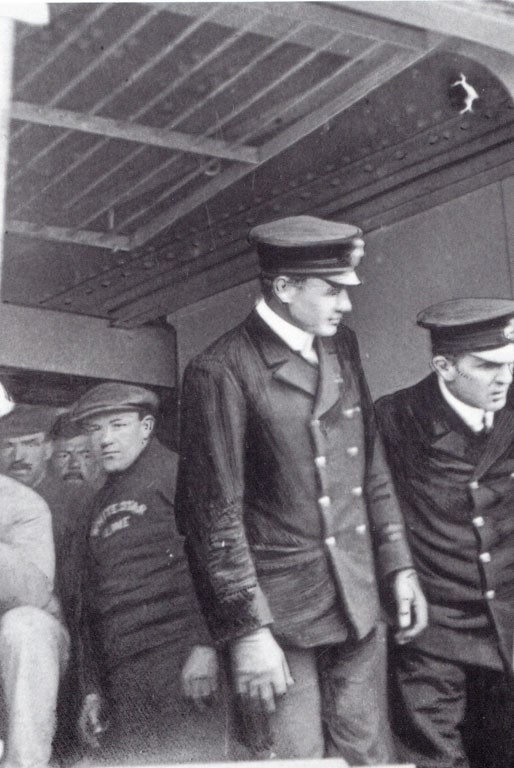 An open gangway with two officers, fourth Boxhall and second Lightoller, and crew. Picture taken from a tender at Queenstown.