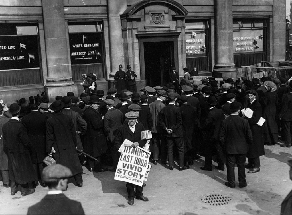 "Crowds outside White Star Line's London offices. A newspaper seller is pictured in the foreground holding a large poster which reads ""Titanic's last hour vivid story, Evening News"""