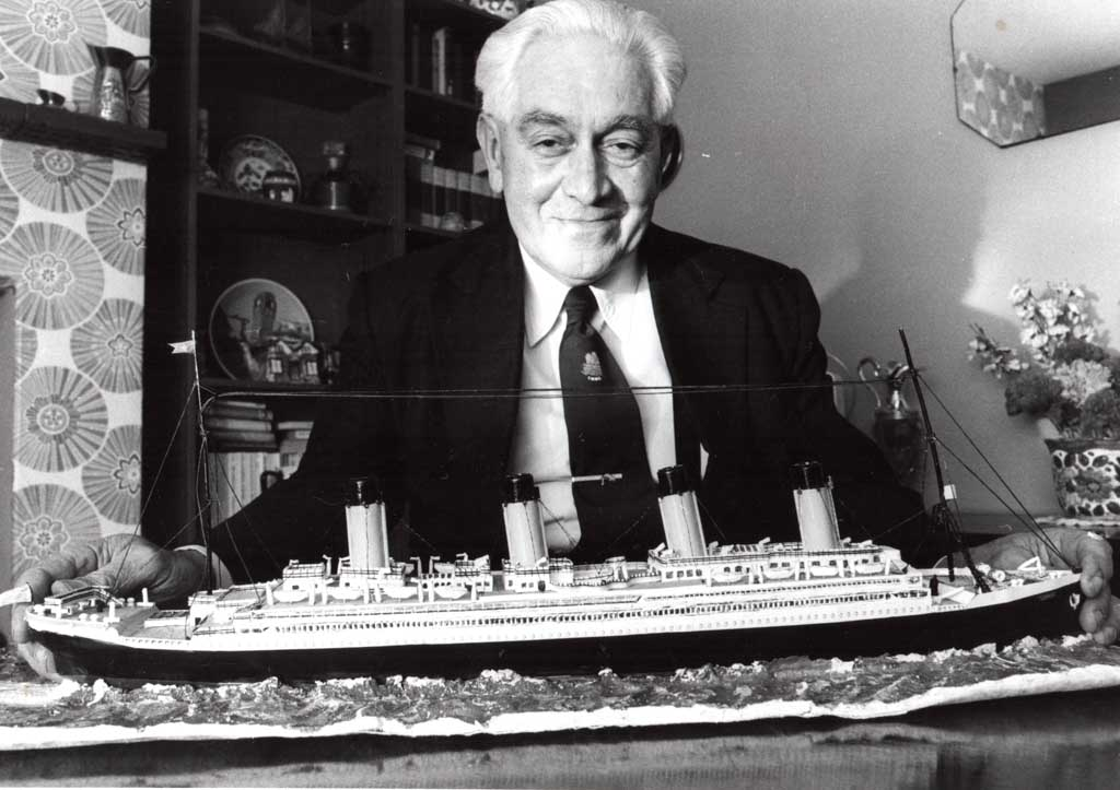 Black and white photograph of Bertram Dean, brother of Millvina. He is smiling and holding a large model of the Titanic.