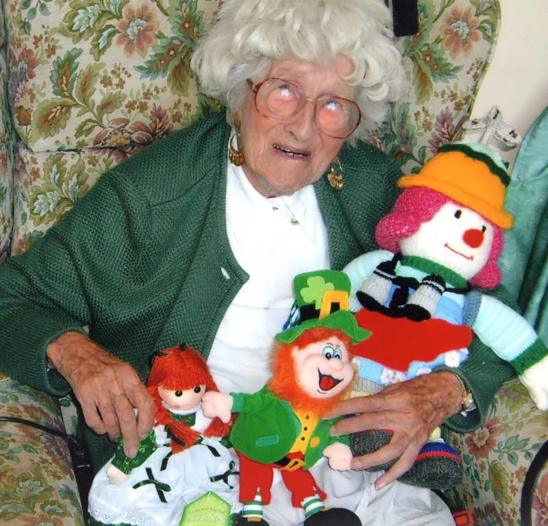 Titanic survivor Millvina Dean, sat down holding several cuddly toys.