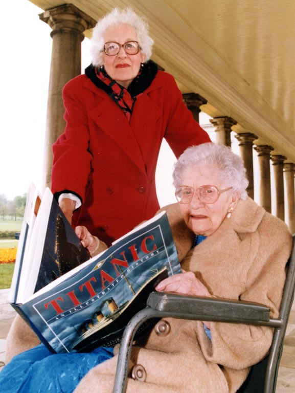 Titanic survivors Millvina Dean & Edith Haisman. Edith is sat in a wheelchair and Millvina stands behind her as they both hold open a large Titanic book.