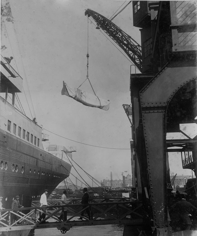 Extra lifeboats are hastily loaded on board Olympic. The side of the liner is visible as a large crane swings a collapsible boat onto the deck.