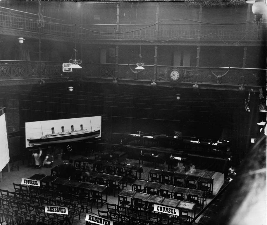 The Drill Hall awaiting the start of proceedings. The hall is empty apart from two men who are securing a huge model of the Titanic at the front for reference.