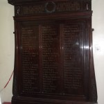 Large polished wood First World War memorial bearing dozens of names