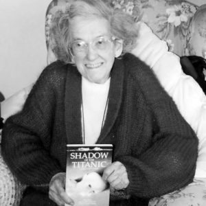 Eva Hart in later years, smiling and holding her autobiography shortly after its publication