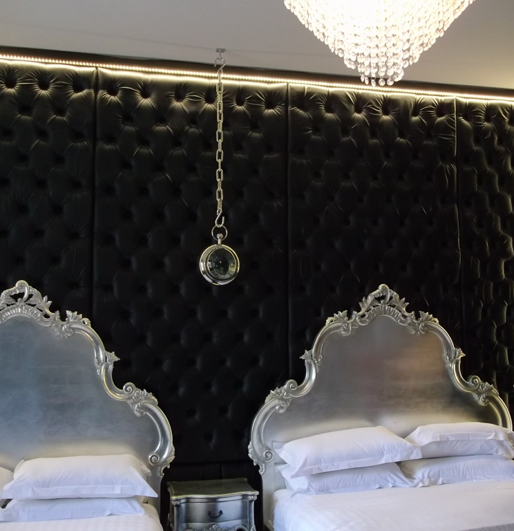 Interior of hotel room with black 'chesterfield style' padded wall with two large beds in front
