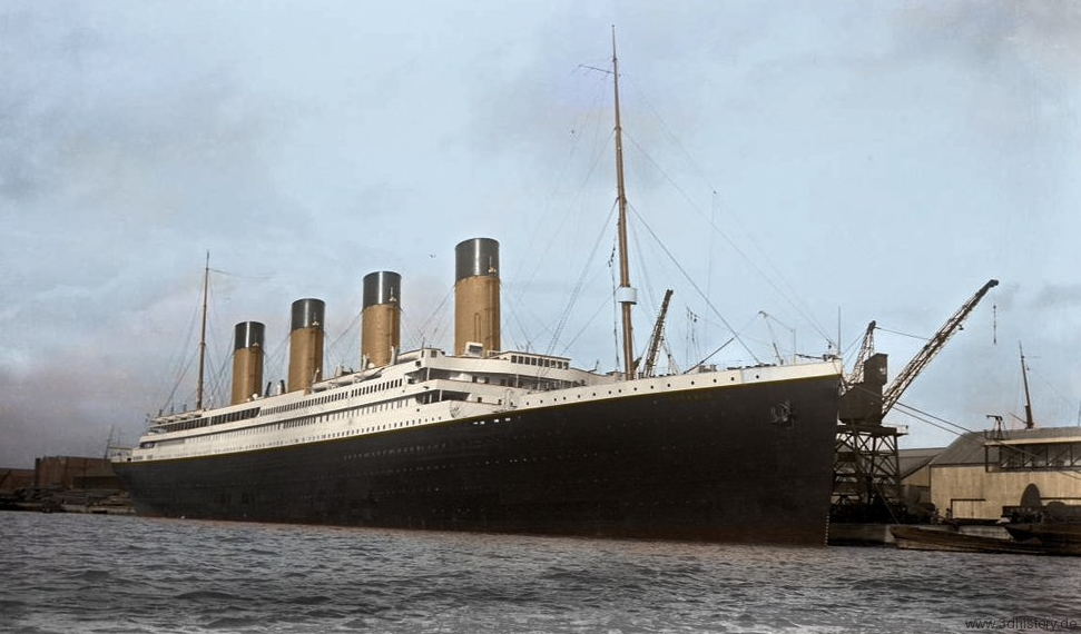 An original image of the Titanic digitally coloured.Titanic is docked and her yellow funnels stand out against a pale blue sky and surrounding drab warehouses.