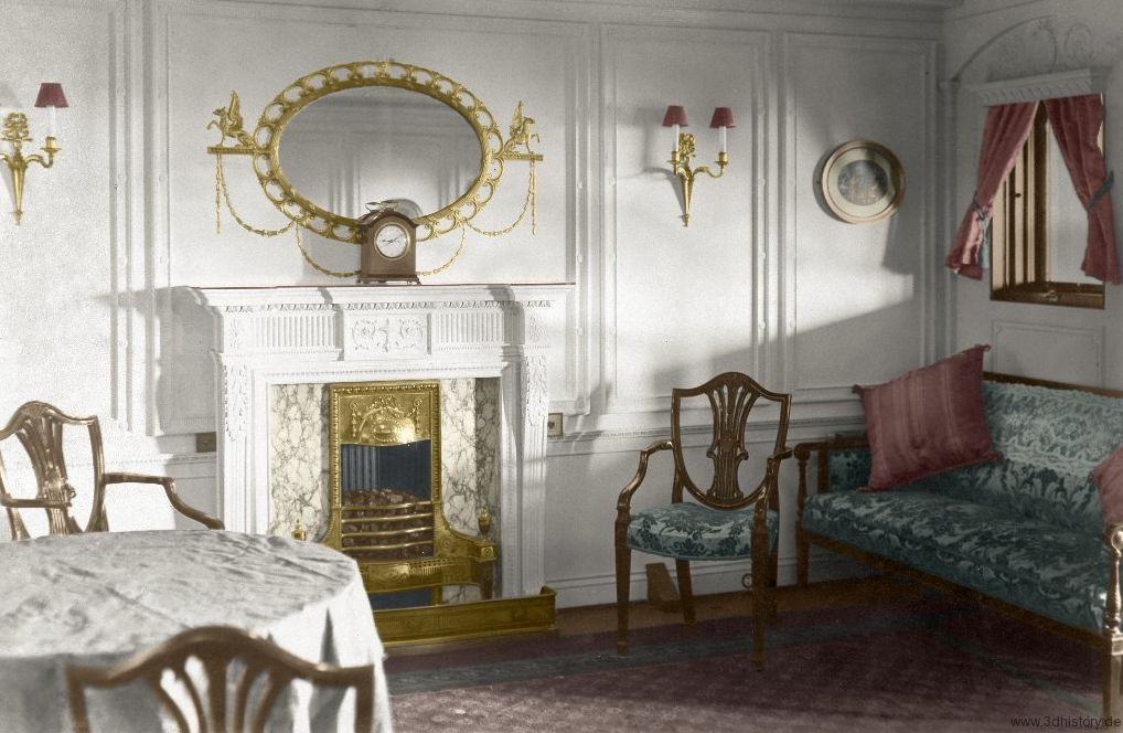 Sitting room from a first class suite. A table, two chairs and green covered settee sit on a pink carpet surrounded by white panelled walls with a white fire surround and gold fireplace, topped by a large gold framed mirror.