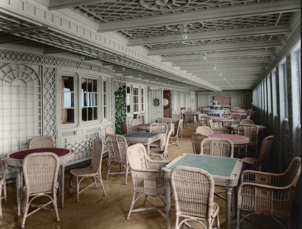 Original photograph digitally coloured of Titanic's Cafe Parisienne. White wicker chairs and tables sit in bright white covered promenade deck surrounded by trellis and an ivy.