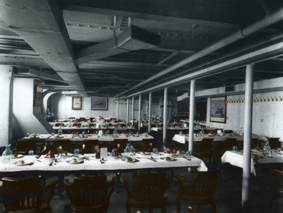 Digitally coloured picture of Titanic's third class dining room. Nine long tables each with eight wooden chairs. Places are set with a menu in the middle and bread rolls on side plates awaiting diners.