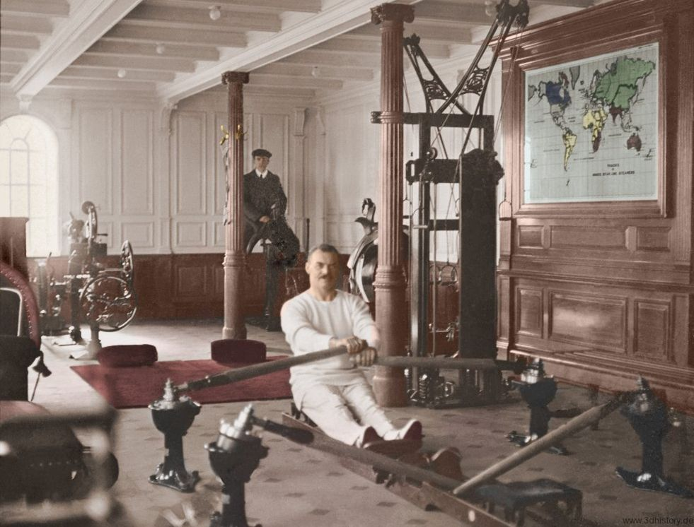 Colour picture of Titanic's gymnasium with the instuctor T.W. McCawley demonstrating the rowing machine, and an electrician in the background testing the mechanical camel!