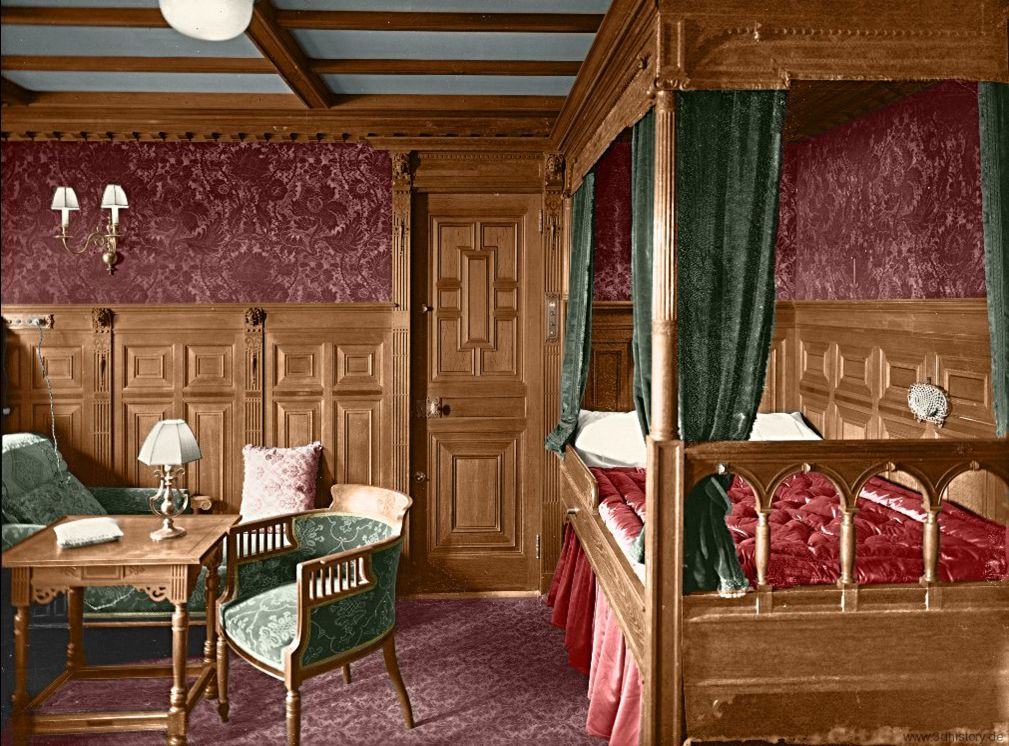 Coloured image of a First Class cabin on Titanic. Wooden panelling fills the bottom half of the wall contrasting with burgundy wallpaper and patterned carpet. There is a wooden panelled bed with green curtains and green chairs, chaise lounge and wooden table. Very nice!
