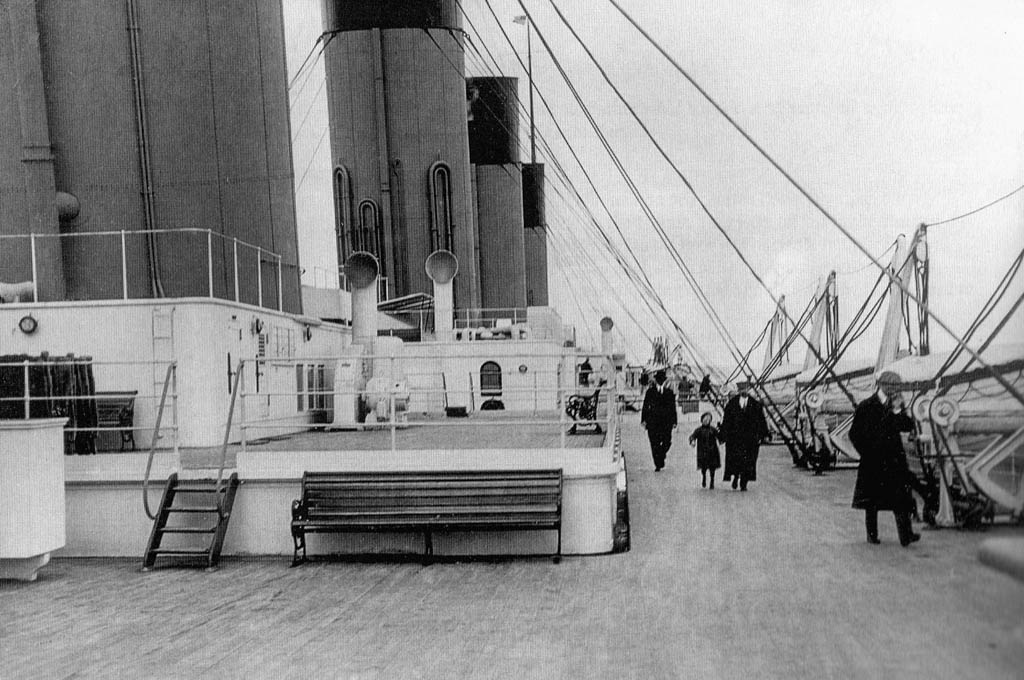 Second class passengers walk along the boat deck