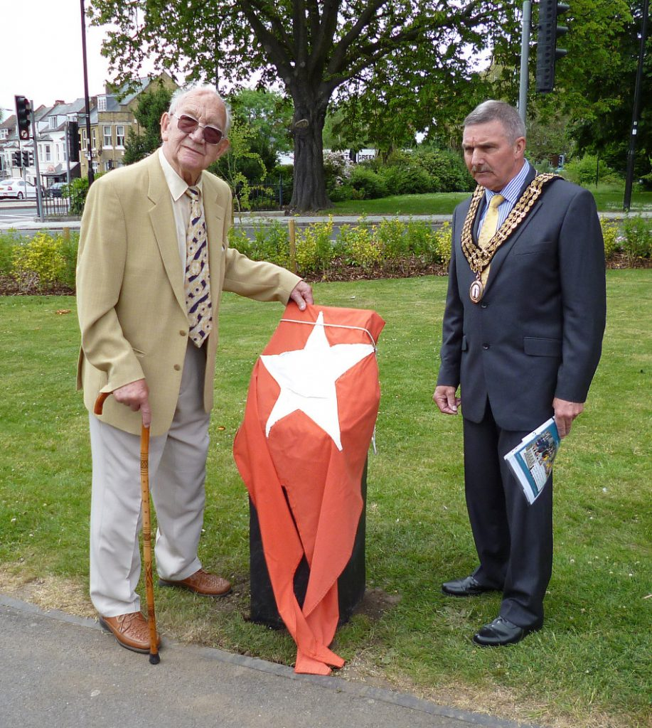 Bruno Normandis and the Mayor of Southampton, Councillor Derek Burke stand by the waist-high slate plinth memorial which draped in ahuge red and white White Star Line flag.